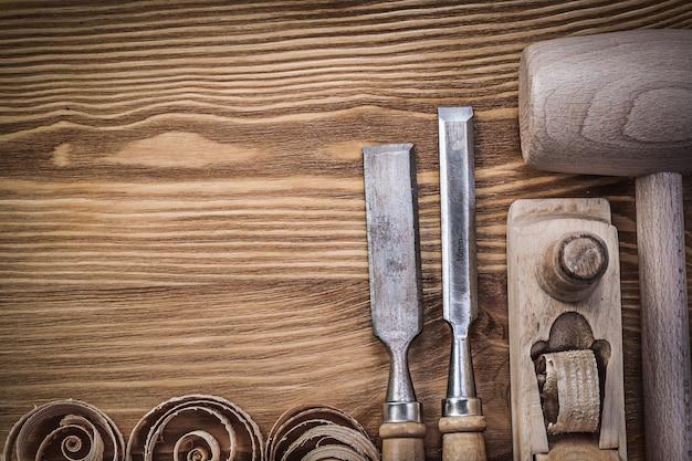 Cepillo de martillo de madera cinceles virutas rizadas sobre tablero de madera vintage