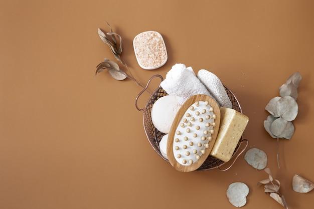 Cepillo de masaje, bombas de baño, jabón y toalla en la canasta sobre fondo marrón vista superior.