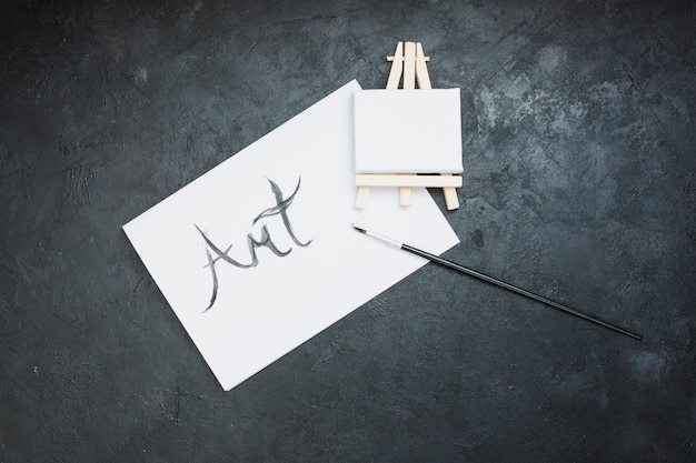 Cepillo de pintura; mini caballete y papel de arte sobre fondo negro.