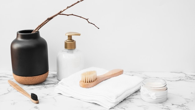 Cepillo; toalla; crema hidratante y botella cosmética sobre superficie de mármol.