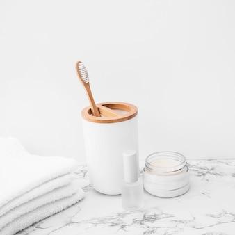 Cepillo; toallas; barniz de uñas y crema hidratante sobre superficie de mármol.