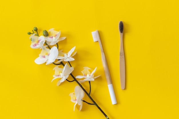 Cepillos de bambú ecológicos naturales y flor de orhid sobre papel fondo amarillo
