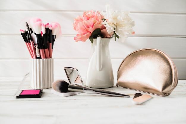 Cepillos y cosméticos cerca de flores y bolsa