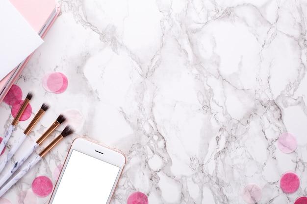 Cepillos cosméticos y teléfono móvil sobre mármol.