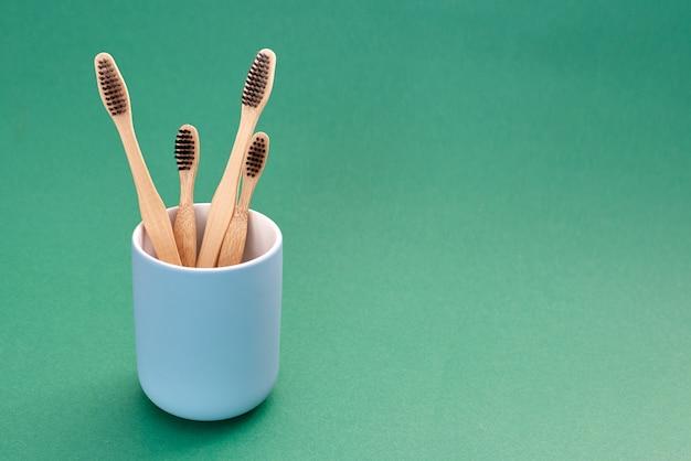 Cepillos de dientes de bambú de varios tamaños en soporte de cerámica azul