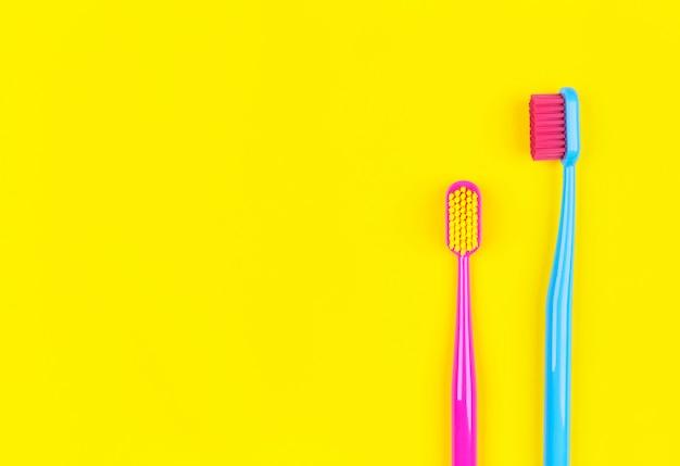 Cepillos de dientes sobre un fondo amarillo con lugar para texto