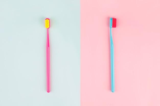 Cepillos de dientes sobre fondo rosa, azul con lugar para el texto.