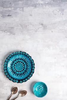 La cerámica turca adornó la placa y el cuenco azules con las cucharas en el fondo de piedra, visión superior