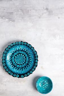 La cerámica turca adornó la placa y el cuenco azules en el fondo de piedra, visión superior