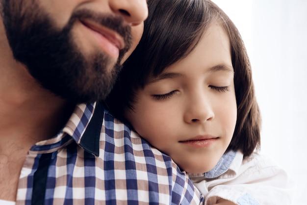 De cerca. el adolescente abraza al padre adulto.