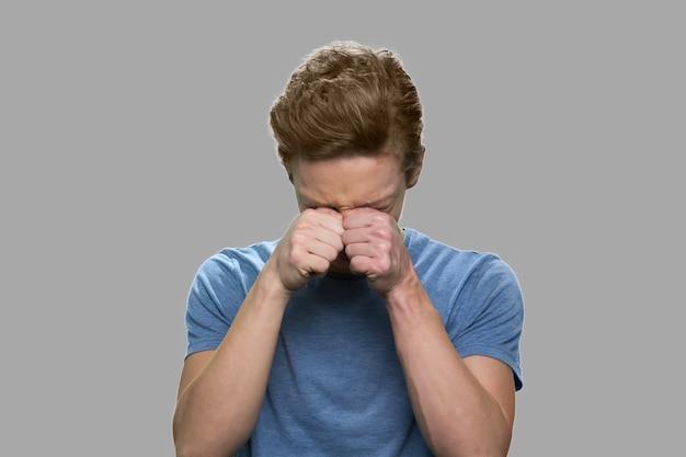 Cerca de adolescente cansado frotándose los ojos. retrato de chico adolescente agotado sobre fondo gris. síndrome de visión por computadora. concepto de fatiga o exceso de trabajo.