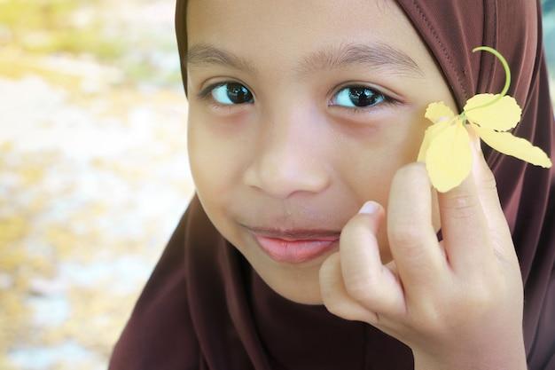 Cerca de la adorable niña musulmana cara vistiendo hijab, sonriendo y sosteniendo la flor amarilla.