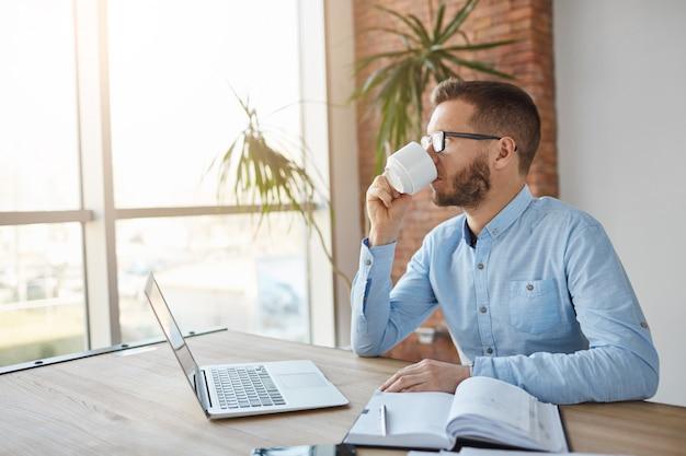 Cerca de adultos de raza caucásica hombre de negocios masculino caucásico con gafas sentado en la oficina