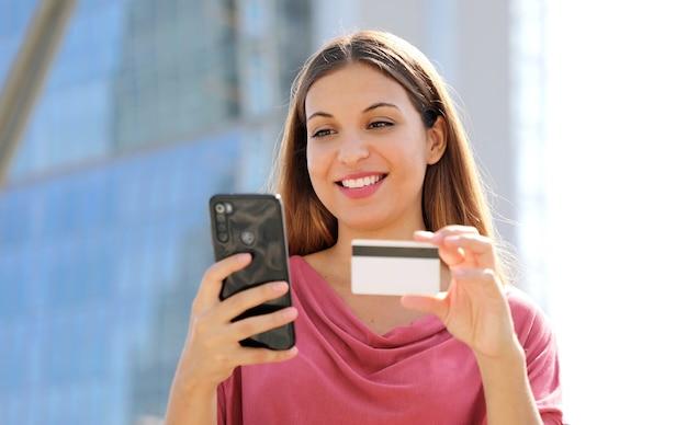 Cerca de agradable mujer encantada con tarjeta de crédito y uso de smartphone al aire libre