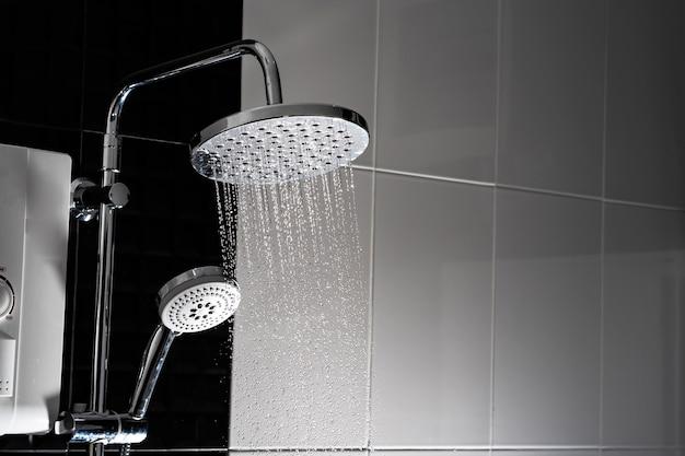Cerca del agua que fluye de la ducha en el baño