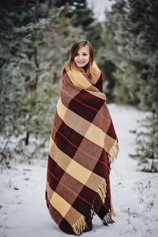 Cerca al aire libre retrato de joven hermosa niña sonriente feliz con manta en el bosque. modelo posando en un parque cubierto de nieve. concepto de vacaciones de invierno. temporada de caminatas invernales heladas.