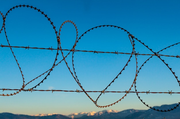 Cerca de alambre de púas contra el cielo azul y las montañas. restricción, propiedad privada