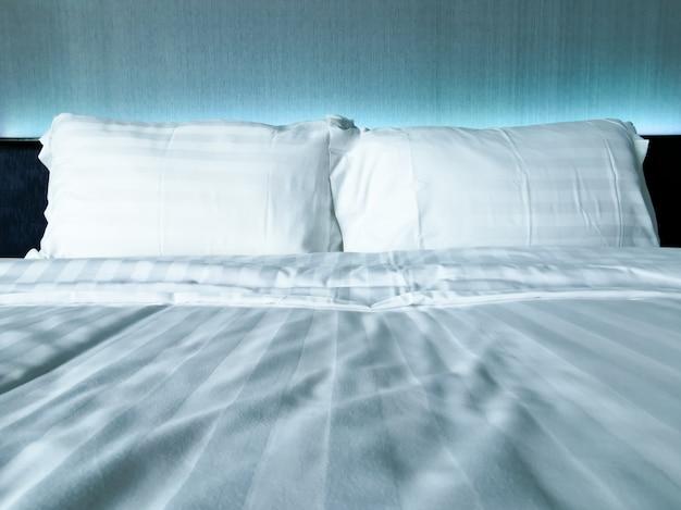 Cerca de la almohada blanca en la cama blanca de confort