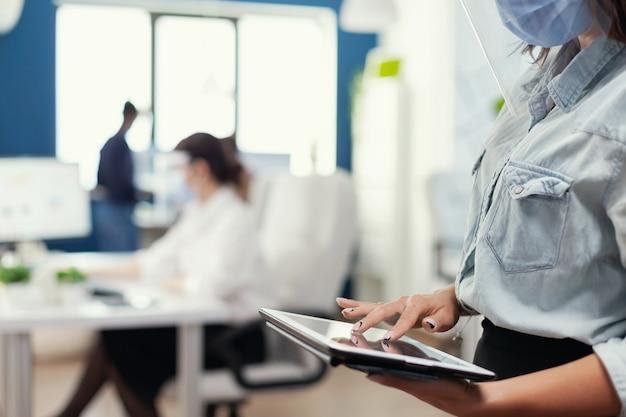 Cerca del analista financiero que controla los gráficos de la gran corporación con tablet pc. compañeros de trabajo multiétnicos que respetan la distancia social en la empresa durante la pandemia de coronavirus.