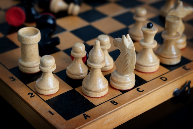 Cerca del antiguo tablero de ajedrez con un conjunto de piezas de madera en blanco y negro de pie en posición caótica