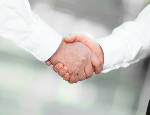 De cerca. apretón de manos de socios comerciales sobre fondo borroso. el concepto de asociación