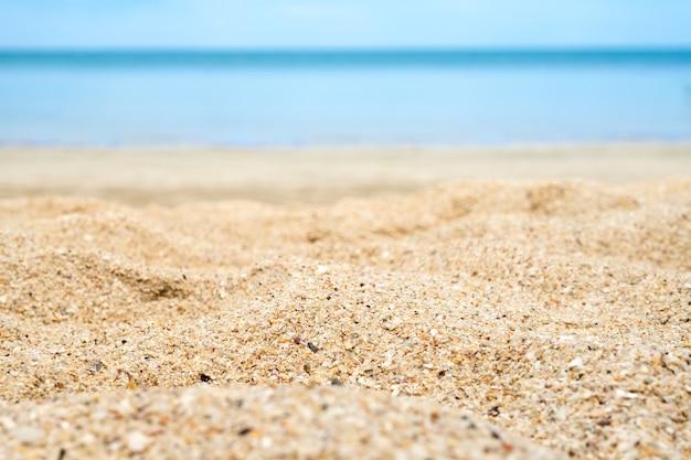 Cerca de la arena de la playa con el mar de desenfoque en el fondo