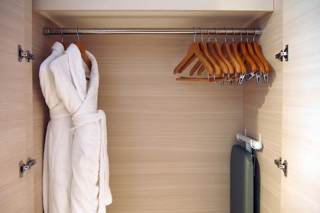 Cerca del armario con percha de ropa de madera