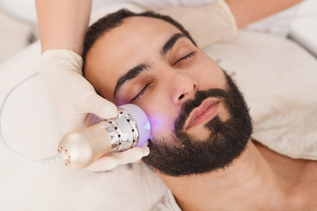 Cerca de un atractivo hombre barbudo que se relaja en la clínica de belleza, obteniendo un facial de levantamiento de rf