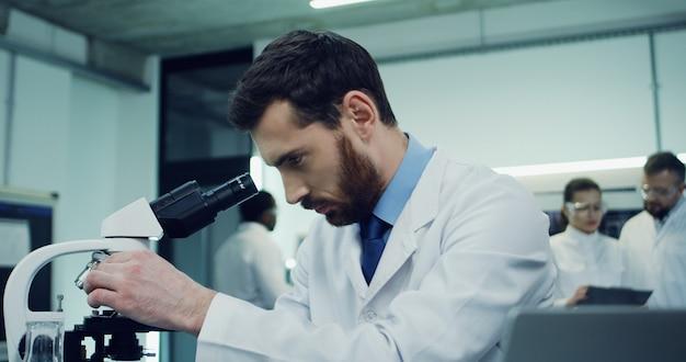 Cerca del atractivo hombre caucásico que trabaja en el laboratorio y mira en el microscopio, luego escribiendo en la computadora portátil. cámara alejándose.