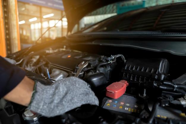 De cerca, el automóvil de servicio es la gente está reparando un automóvil use una llave inglesa y un destornillador para trabajar.