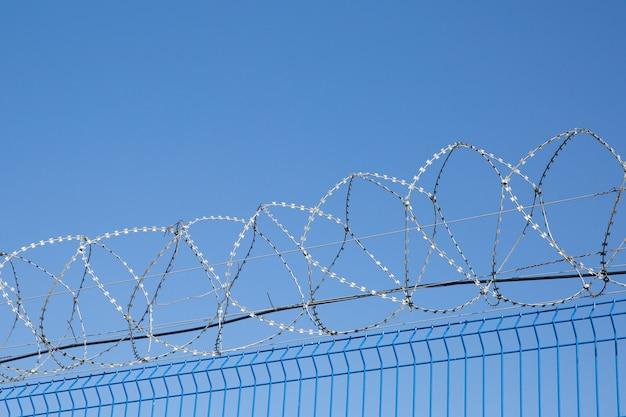 Cerca azul con alambre de púas en fondo del cielo azul. zona peligrosa.