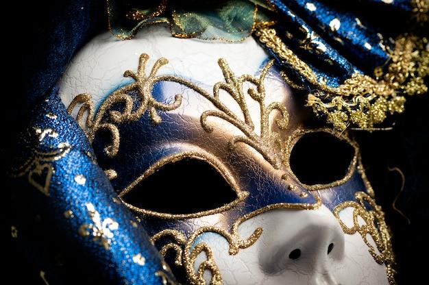 Cerca de un azul con máscara veneciana tradicional elegante de oro sobre fondo blanco