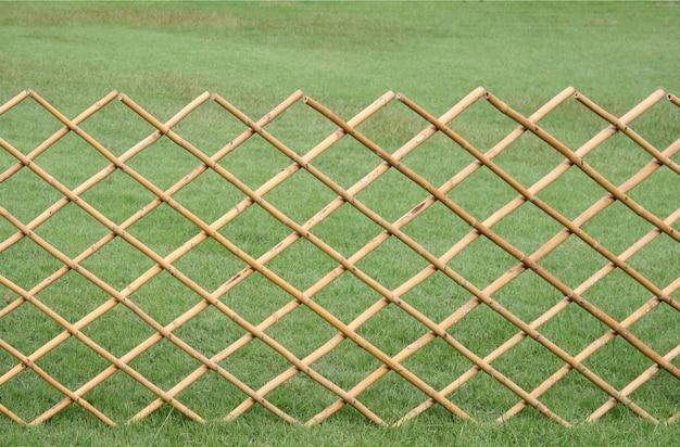 Cerca de bambú sobre fondo de jardín de hierba verde
