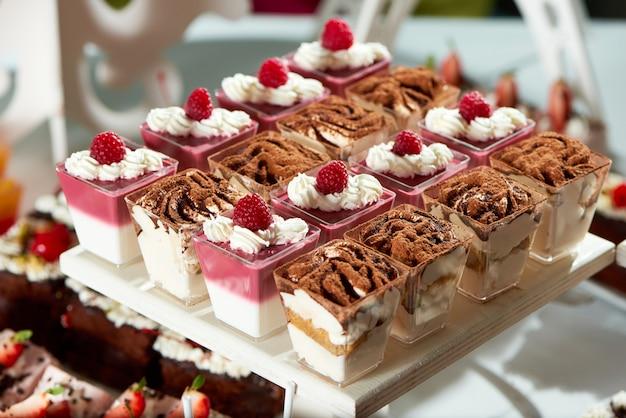 Cerca de una bandeja llena de deliciosos postres de gelatina con sabor a frambuesa y chocolate, crema batida, bayas, chocolate, cacao, tiramisú, receta, cocina, cocina, fiesta, buffet de dulces.