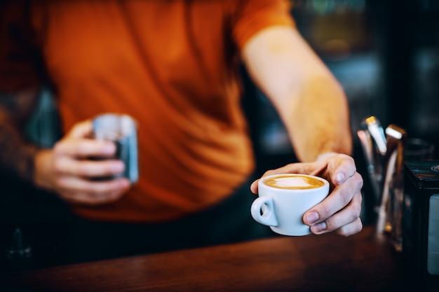Cerca del barman sosteniendo una taza de espresso fresco de la mañana y entregárselo a un cliente.