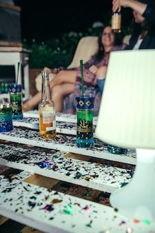 Cerca de bebidas sobre mesa de palets con confeti en una fiesta al aire libre con mujeres hablando