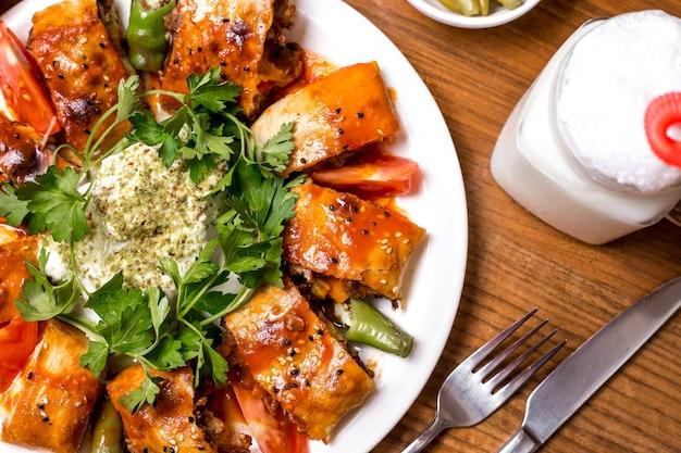 Cerca de beyti kebab servido con ayran y pepinillos