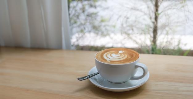Cerca de blanco taza de café con leche caliente con arte de espuma de leche