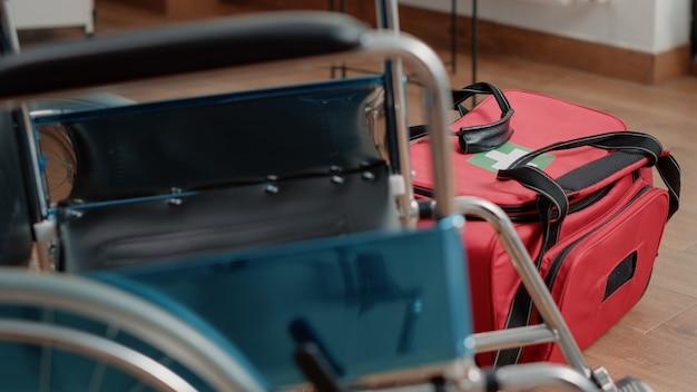 Cerca de la bolsa con equipo médico y silla de ruedas