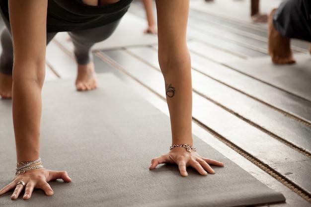 Cerca de los brazos femeninos en pose de tablón