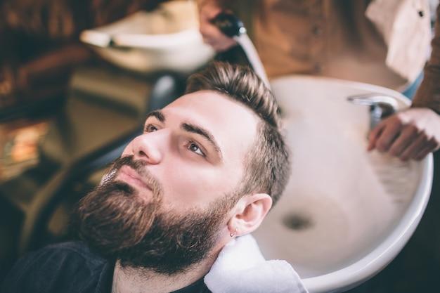 Cerca de la cabeza del cliente que está siendo lavada por el estilista. lo está lavando con agua. el procedimiento es suave y lleno de cuidado.