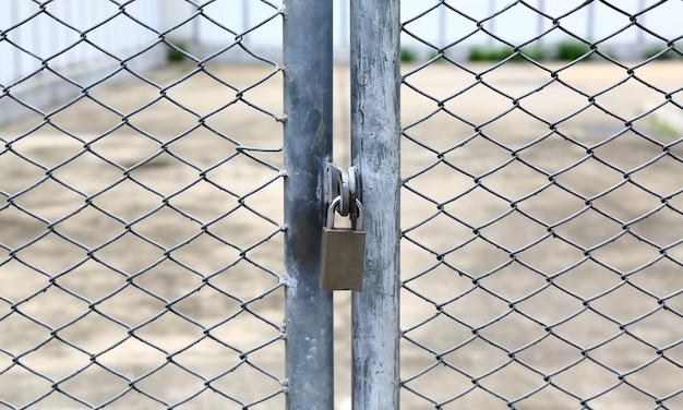 Cerca de la cadena y puerta de metal con cerradura