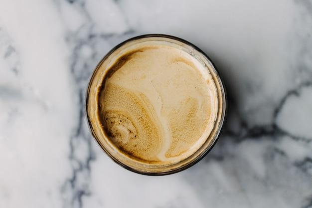 Cerca de café dirty latte con textura de mármol en el café y la mesa.