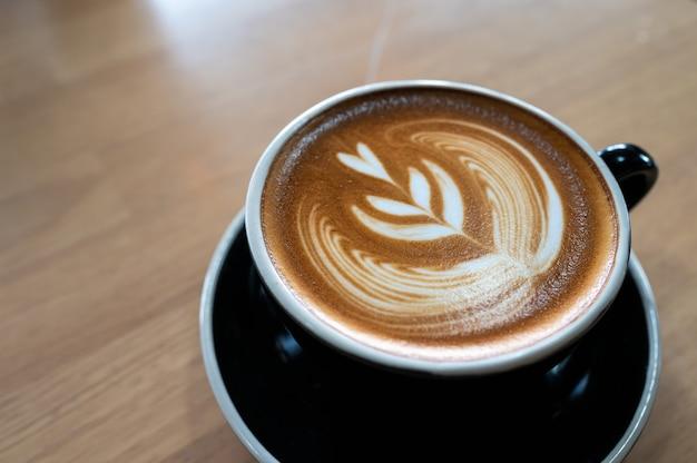 Cerca de café con leche arte en mesa de madera