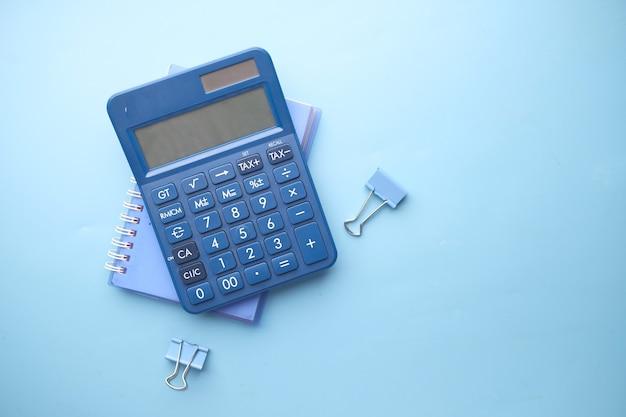 Cerca de la calculadora azul y el bloc de notas en color