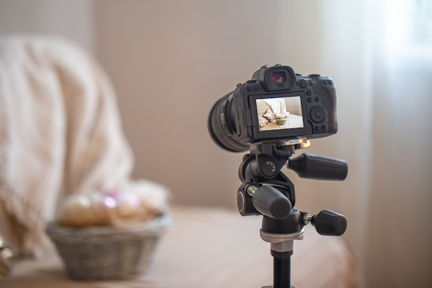 Cerca de una cámara digital profesional en un trípode mientras dispara una composición casera sobre fondo borroso
