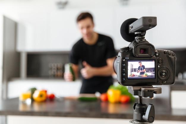 Cerca de una cámara de video filmando joven blogger masculino sonriente