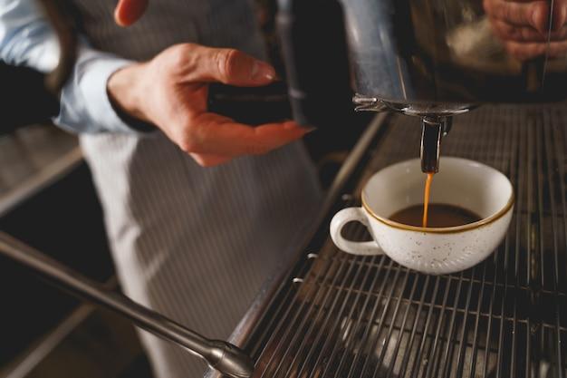 Cerca del camarero vertiendo bebida caliente en una taza blanca del grifo de la máquina de café