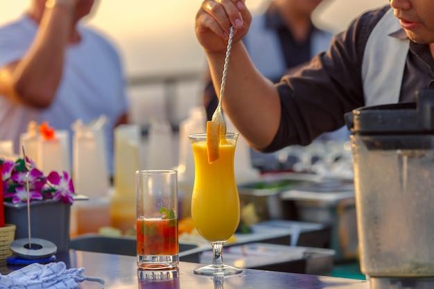 Cerca de los camareros en el proceso de preparación de la mezcla de jugo de naranja para los clientes