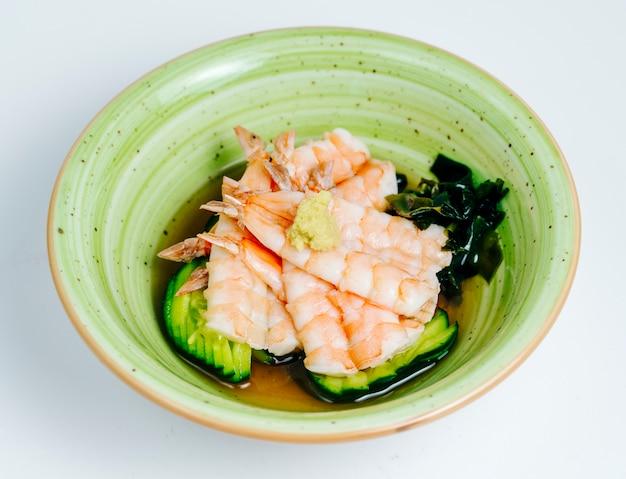 Cerca de camarones sopa de miso servido en un tazón verde manzana en fondo blanco.